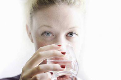 Jeune femme qui boit un verre d'eau pour s'hydrater