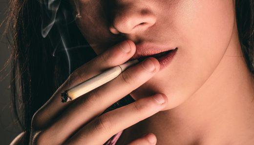 Jeune femme qui fume une cigarette malgré les risques de problèmes dentaires