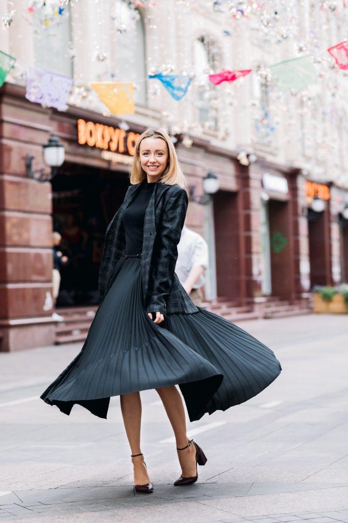 femme blonde portant un jupe midi plissée foncée des babies pointues à talons un pull noir et un blazer à carreaux