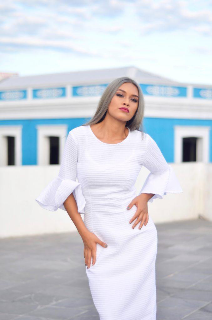 femme portant un robe blanche près du corps avec manches à volants