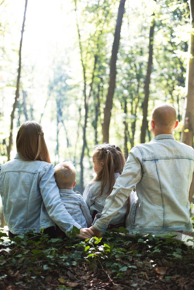 membres d'une famille portant une veste en jean assis dans la forêt