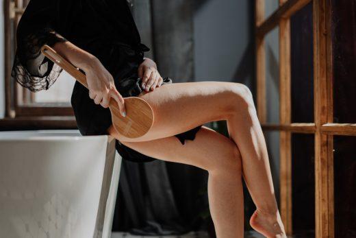 jeune femme assise sur le bord d'une baignoire qui fait un traitement anti-cellulite