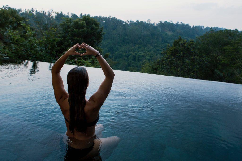femme assise dans l'eau qui fait un cœur avec ses mains